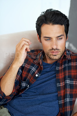 Buy stock photo A gorgeous young man lying on a sofa with an expression of contemplation