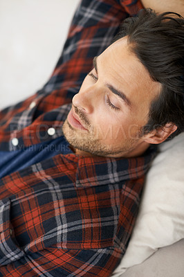 Buy stock photo A gorgeous young man lying down with his arm behind his head