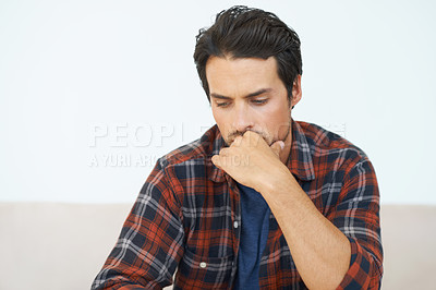 Buy stock photo A gorgeous young man sitting on a sofa and looking down with hand rested against his mout and an expression of concern on his face