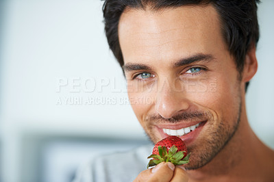Buy stock photo Portrait of a gorgeous young man holding a strawberry and smiling