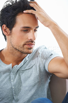 Buy stock photo Profile of a gorgeous young man sitting with hand in hair against a white background