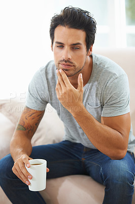 Buy stock photo A gorgeous young man sitting on a sofa with a look of contemplation while holding a cup of coffee
