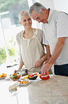 Smiling old aged couple cooking food together