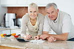 Elderly couple calculating their bills at the kitchen