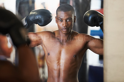 Buy stock photo A muscular african american boxer flexing his biceps