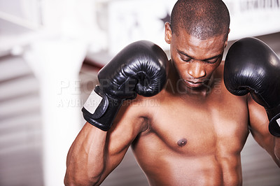 Buy stock photo An african american boxer looking down with his gloves up