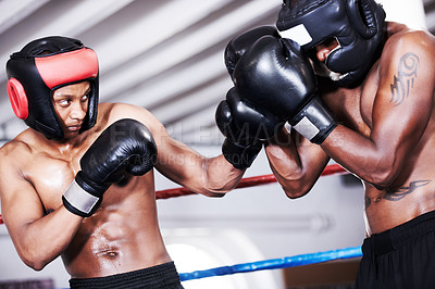 Buy stock photo Two boxers wearing protective gear sparring with one another