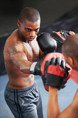 Buy stock photo A young focused boxer sparring with his partner in protective gloves