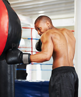 Buy stock photo An african american boxer practicing with a punching ball