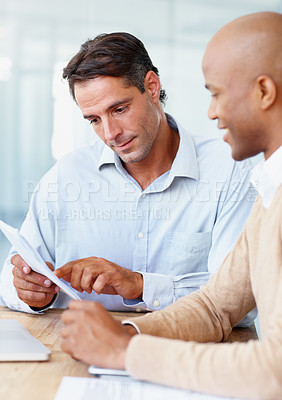 Buy stock photo Two businessman going over documents in the office together