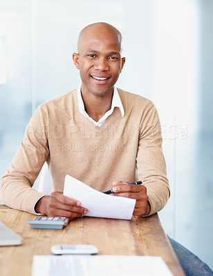 Buy stock photo A handsome african american man calculating expenditure in the office