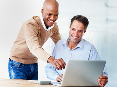 Buy stock photo Two businesspeople working on a laptop together in the office