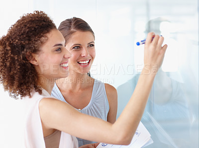 Buy stock photo Two businesswoman working on a whiteboard together