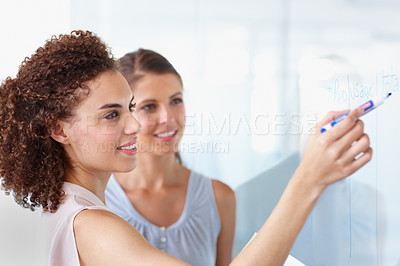 Buy stock photo Two business women working on a whiteboard together