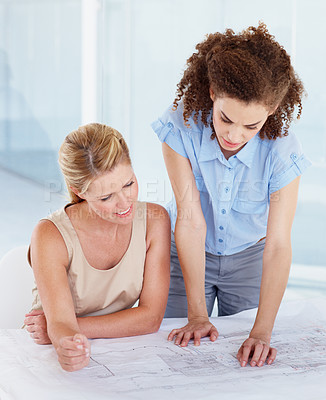 Buy stock photo Two architects looking at blueprints together