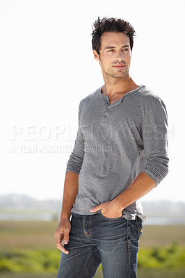 Buy stock photo A handsome young man standing outside with his hands in his pockets