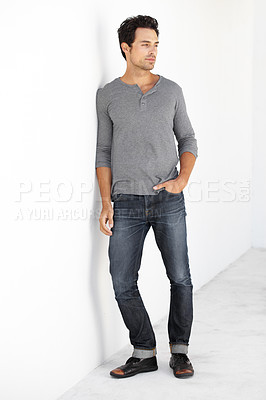 Buy stock photo A handsome young man leaning against a wall with his hand in his pocket