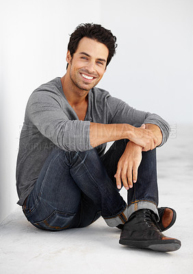 Buy stock photo Portrait of a handsome young man sitting crossed-legged and smiling happily