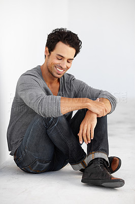 Buy stock photo A handsome young man sitting crossed-legged and smiling with his eyes closed