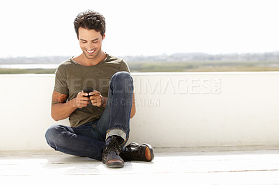 Buy stock photo A handsome young man sending a text message while sitting outside