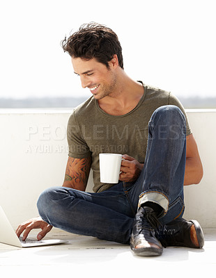 Buy stock photo A handsome young man sitting outside with his coffee while using his laptop
