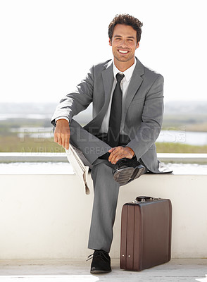 Buy stock photo Portrait of a handsome young businessman sitting outside with his briefcase and a newspaper
