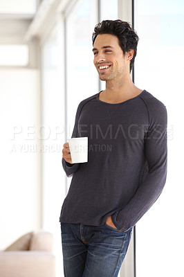 Buy stock photo A handsome young man relaxing at home with a cup of coffee