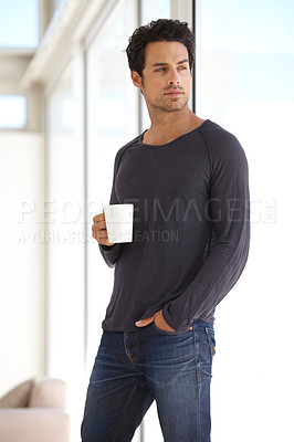 Buy stock photo A handsome young man holding his morning coffee and thinking about the day ahead