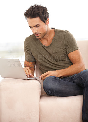 Buy stock photo A handsome young man surfing the net on his laptop at home