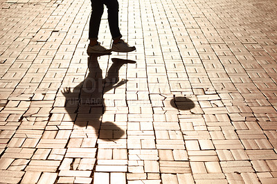 Buy stock photo Cropped image of a single pair of legs kicking a soccer ball casting a shadow