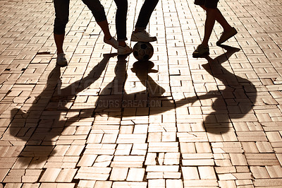 Buy stock photo Cropped image of legs kicking a ball with shadows on the paved road