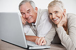 Older couple using a laptop while lying on the floor