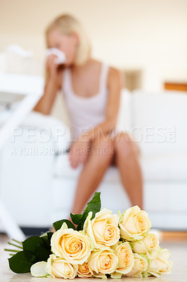 Buy stock photo A young woman sneezing in the background with roses lying on the floor