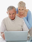 Thoughtful older couple working on a laptop