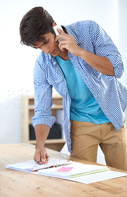 Buy stock photo Shot of a handsome young man talking on his cellphone while in the office