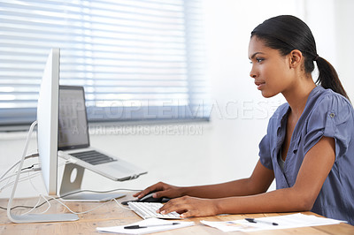 Buy stock photo Beautiful young ethnic woman working on her computer in the office