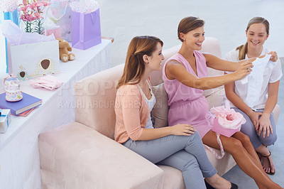 Buy stock photo A young pregnant woman receiving baby clothes from her pretty friends at her babyshower