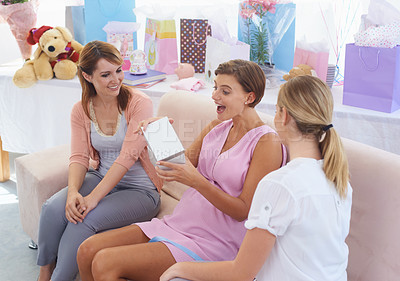 Buy stock photo A pregnant woman excited and surprised by what her friends have given her