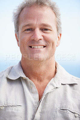 Buy stock photo Head and shoulders portrait of a mature man smiling happily at the camera