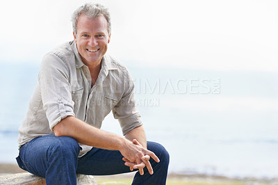 Buy stock photo Portrait of a rugged man sitting outdoors and smiling at the camera
