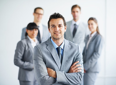 Buy stock photo Portrait of a handsome young businessman with his colleagues standing in the background