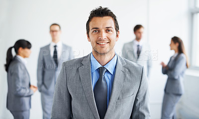 Buy stock photo Portrait of a handsome young businessman smiling while his colleagues stand blurred in the background