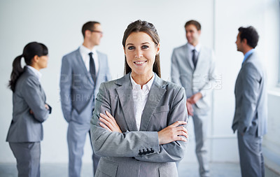 Buy stock photo A pretty young businesswoman smiling at you while her colleagues stand in the background