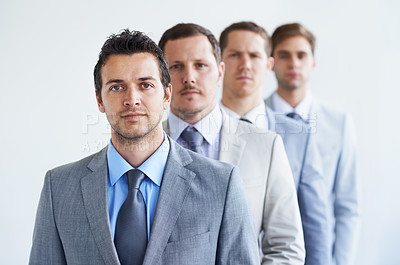 Buy stock photo Portrait of a group of serious businessman standing in a line
