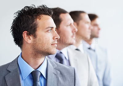 Buy stock photo A line of businesspeople looking away thoughtfully - Ambition