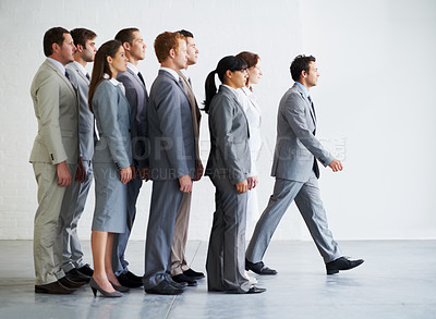 Buy stock photo A young business manager walking ahead of his colleagues - Leadership