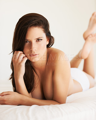 Buy stock photo Beautiful young woman lying naked on a bed looking at the camera