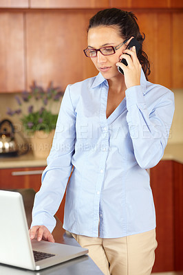 Buy stock photo Shot of a young businesswoman standing in her kitchen working on a laptop and talking on the phone