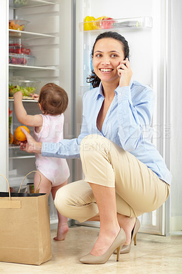 Buy stock photo Shot of a mother talking on the phone while putting groceries away with her baby rummaging through the fridge
