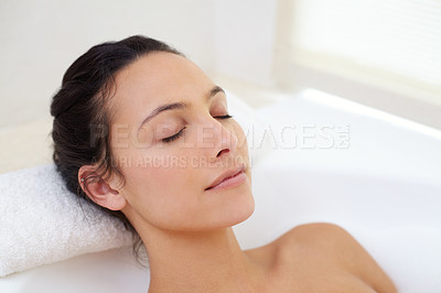 Buy stock photo Cropped shot of a beautiful young woman relaxing in the bathtub
